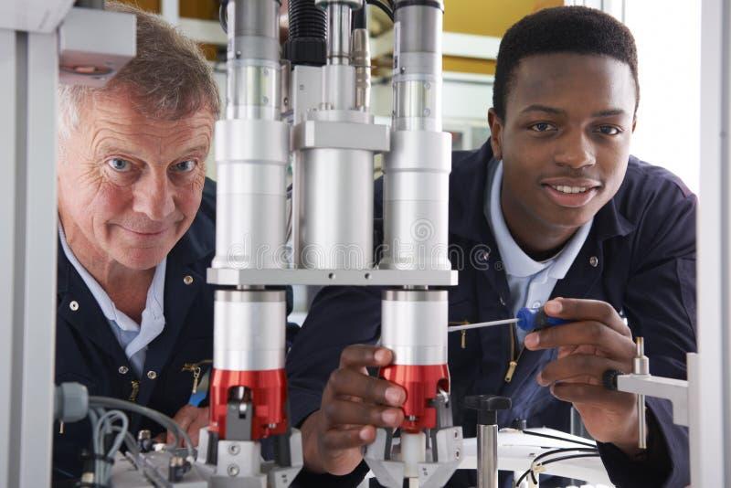Ingenieur And Apprentice Working op Machine in Fabriek stock afbeeldingen