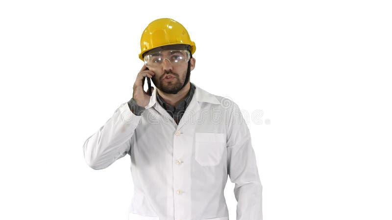 Ingenieur in beschermende glazen en hoed lopen, die de telefoon op witte achtergrond overnemen royalty-vrije stock afbeeldingen