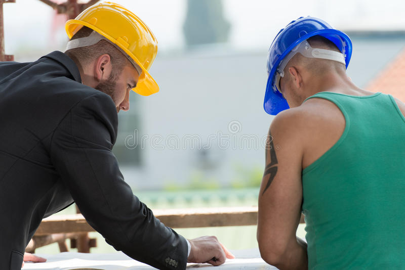 Ingenieur And Construction Worker die een Project bespreken stock foto's