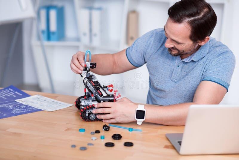 Ingenieur in den blauen T-Shirts, die droid konstruieren lizenzfreies stockbild