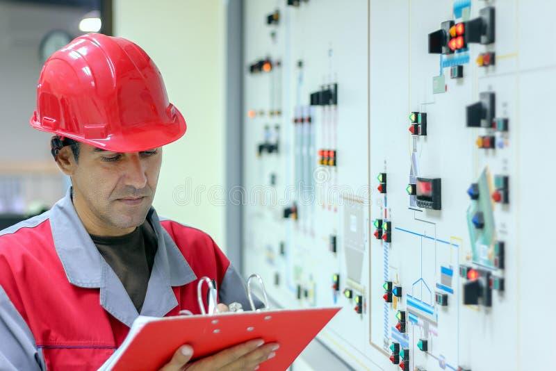 Ingenieur, der in einem Power Plant Control Room auf der Zwischenablage schreibt lizenzfreies stockbild