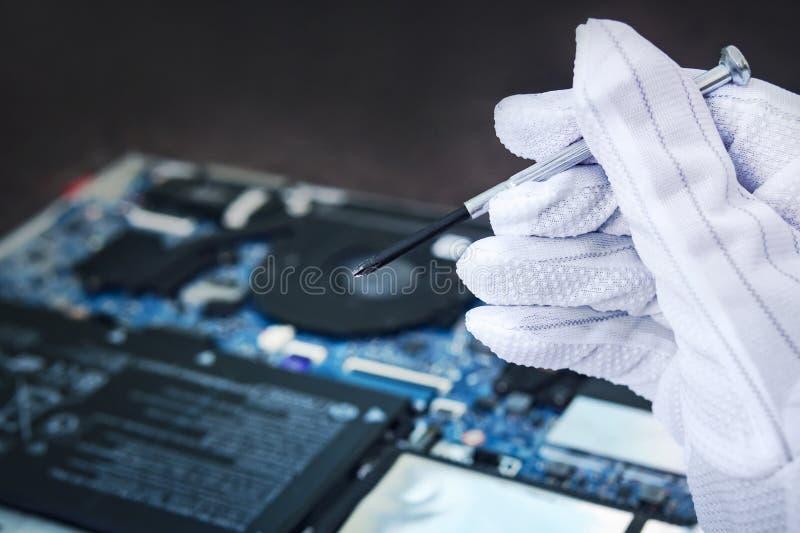 Ingenieur, der gebrochenen Computer bei der Arbeit regelt IT-Techniker, der gebrochenen Laptopnotebook repariert Elektronische Re stockfoto