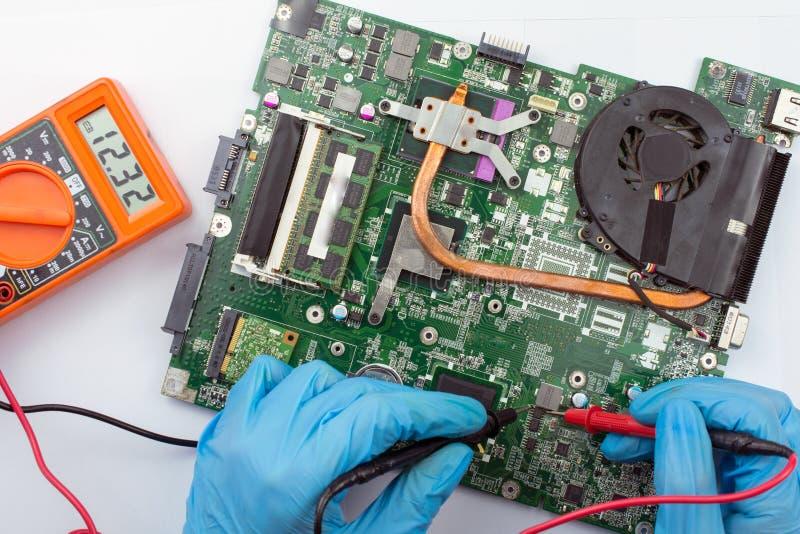 Ingenieur, der gebrochenen Computer bei der Arbeit regelt stockbilder