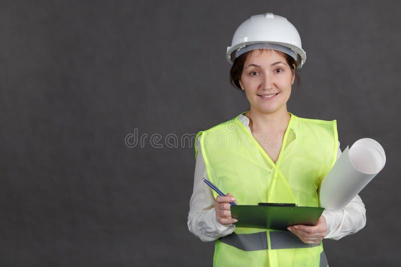 Ingenieur der jungen Frau im Schutzhelm und Weste mit Projekten Macht Anmerkungen in der Tablette stockfotografie