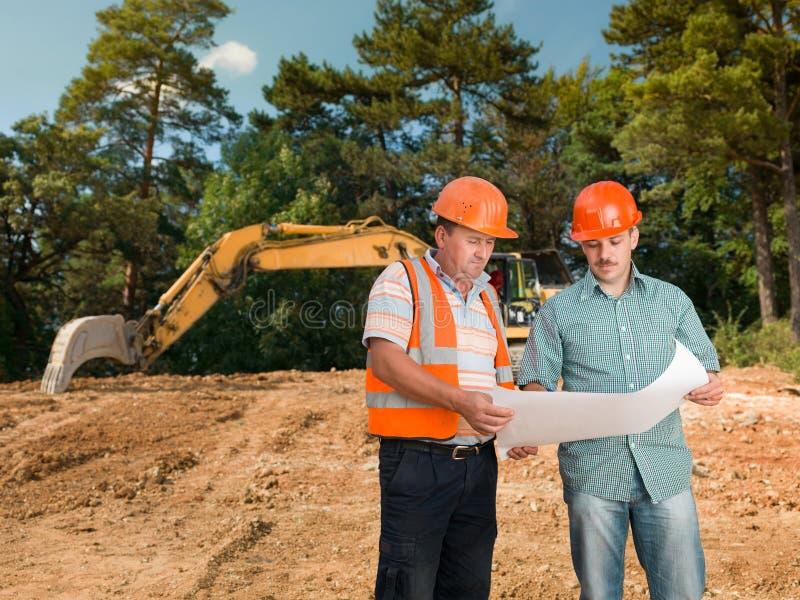 Ingenieur, der Plan mit Bauarbeiter bespricht stockfotos