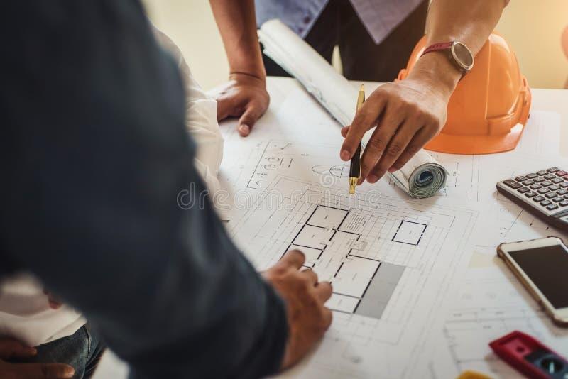 Ingenieur die bij een blauwdruk van huis in bureau voor het bespreken van onroerende goederenproject werken Van de techniekhulpmi stock afbeeldingen
