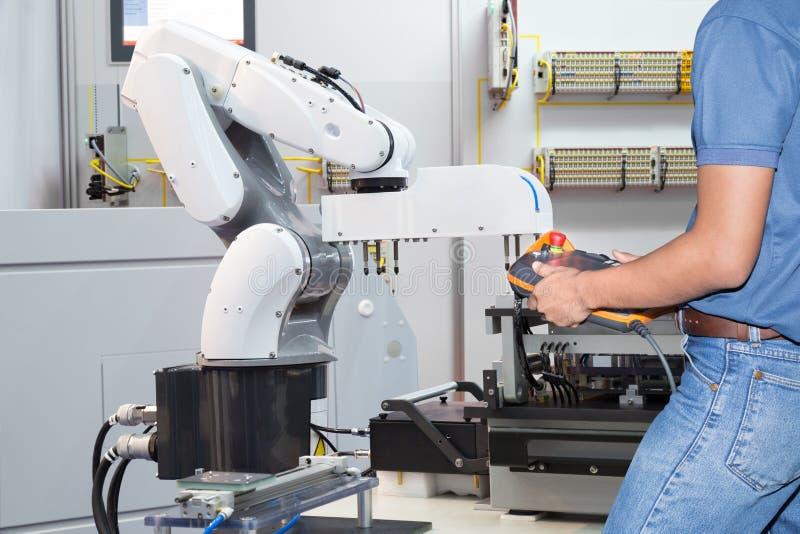 Ingenieur die geautomatiseerde robotachtig voor holdingsassemblage controleren stock foto