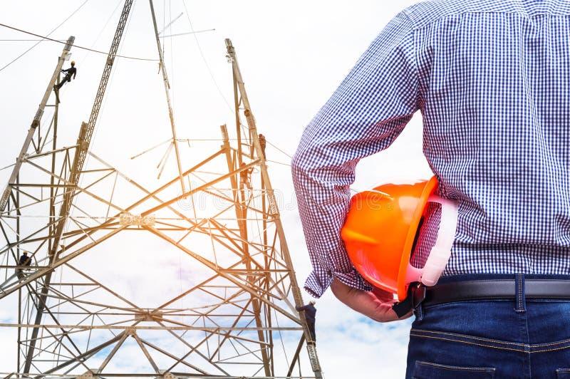 Ingenieur die gele veiligheidshelm met elektriciens houden die aan pylon bouwtoren werken royalty-vrije stock afbeelding