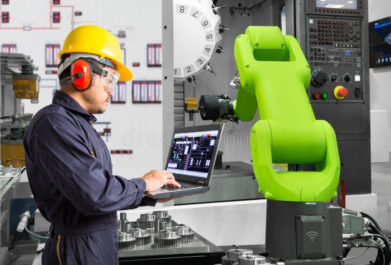 Ingenieur die laptop automatische robotachtige de handwerktuigmachine van de computercontrole met CNC machine in de automobielind royalty-vrije stock foto