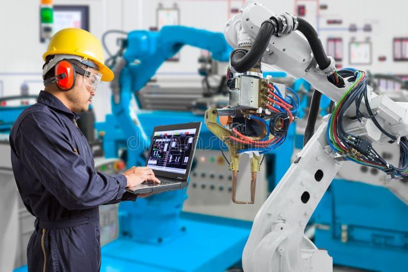 Ingenieur die laptop automatische robotachtige de handwerktuigmachine van het computeronderhoud in de automobielindustrie, Indust stock fotografie