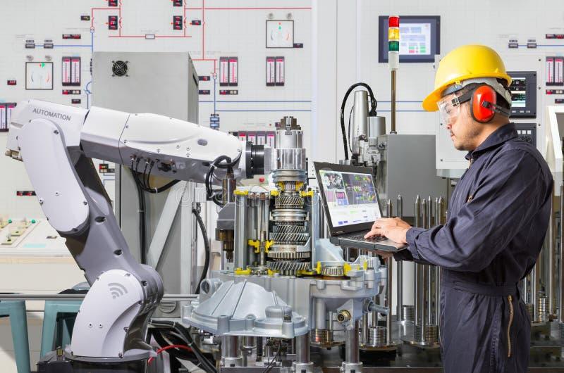 Ingenieur die laptop computer voor de onderhouds robotachtige industrie met behulp van royalty-vrije stock fotografie