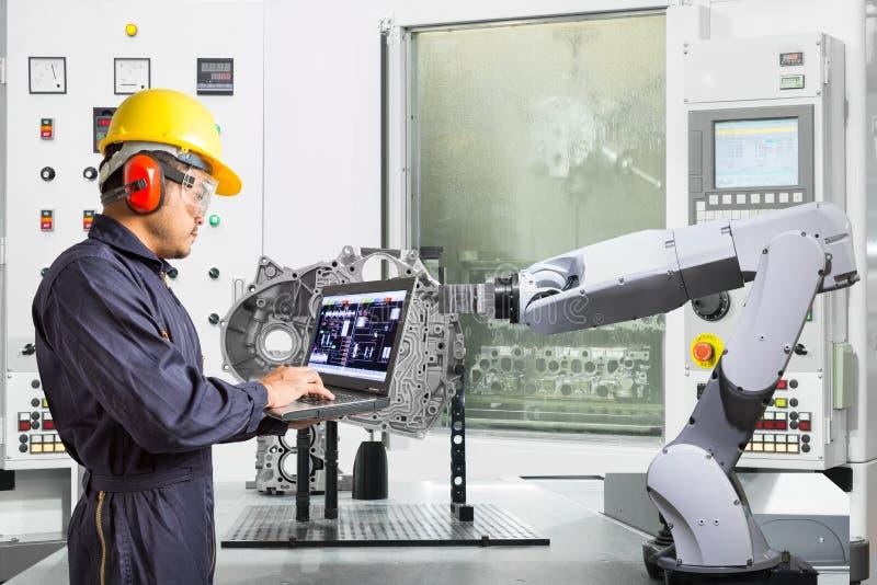 Ingenieur die laptop de automatische robotachtige hand van de computercontrole met CNC machine in de automobielindustrie, Slim fa stock afbeelding