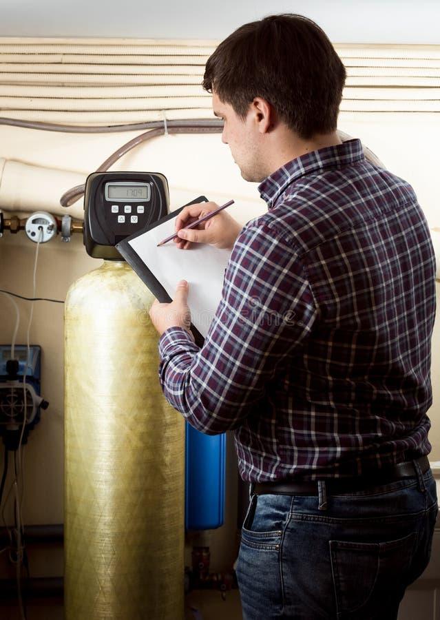 Ingenieur die meterlezing op industriële tellers neerschrijven royalty-vrije stock afbeelding