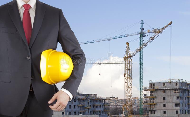 Ingenieur die in zwart kostuum gele helm op bouwwerf houden royalty-vrije stock afbeelding