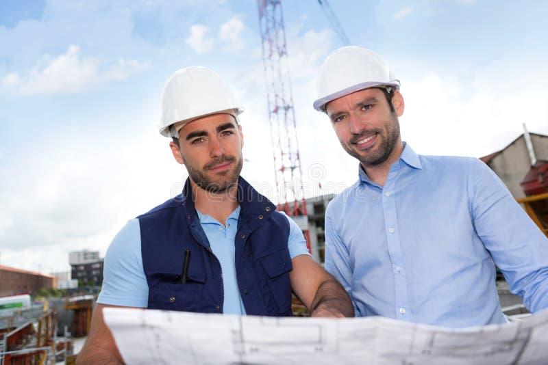 Ingenieur en arbeiders het letten op blauwdruk op bouwwerf royalty-vrije stock foto