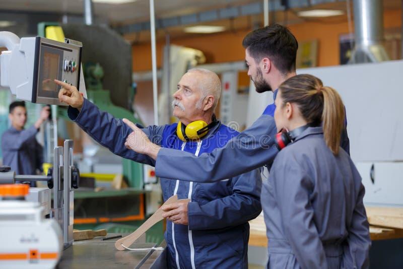 Ingenieur en leerling die geautomatiseerde machines met behulp van royalty-vrije stock foto
