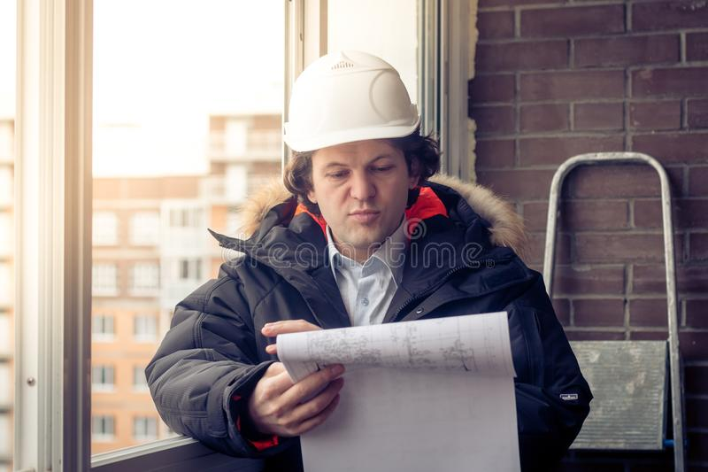 Ingenieur-Erbauer, der mit Dokumenten auf der Baustelle arbeitet Arbeitskraft kontrolliert Zeichnungen auf der Baustelle lizenzfreies stockbild