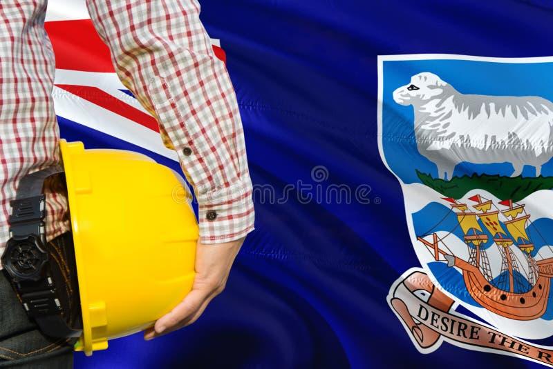 Ingenieur hält gelben Schutzhelm mit dem Wellenartig bewegen des Falkland Islands-Flaggenhintergrundes Bau- und Geb?udekonzept lizenzfreie stockfotografie