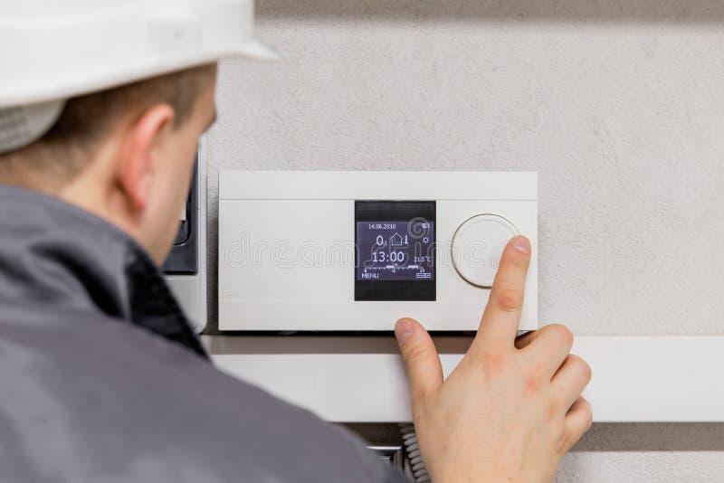 Ingenieur het aanpassen thermostaat voor efficiënt geautomatiseerd verwarmingssysteem