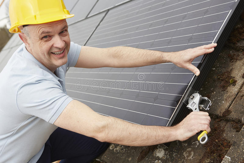 Ingenieur Installing Solar Panels auf Dach des Hauses lizenzfreie stockfotos