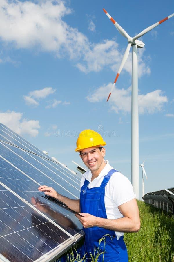 Ingenieur kontrolliert Sonnenkollektoren am Energiepark lizenzfreie stockfotografie