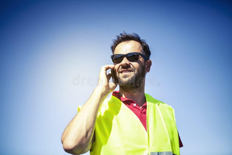 Ingenieur met geel weerspiegelend vest, die door mobiele telefoon spreken royalty-vrije stock fotografie