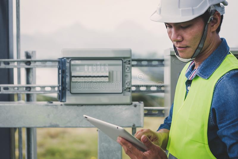 Ingenieur- oder Elektrikerholdinglaptop für kontrollieren und Hauptverteilung durch wifi Technologie überprüfend; intelligente lizenzfreies stockbild