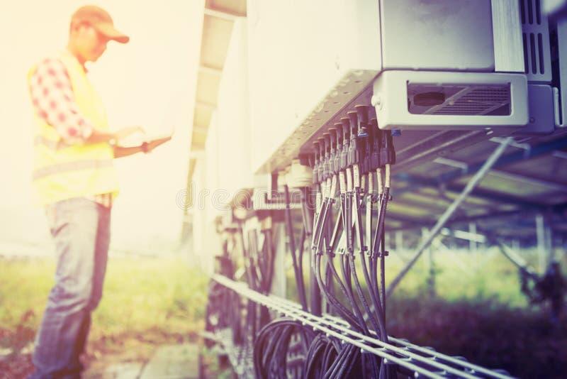 Ingenieur- oder Elektrikerholdinglaptop für kontrollieren und Prüfungschnurinverter durch wifi Technologie; intelligente Techno lizenzfreies stockfoto