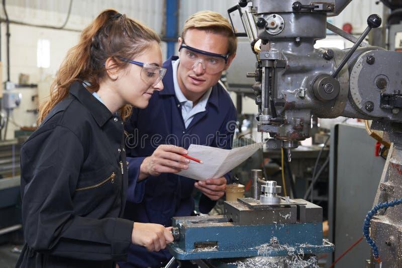 Ingenieur Showing Apprentice How aan Gebruiksboor in Fabriek stock foto