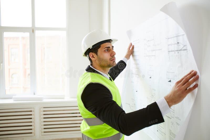 Ingenieur Studying Plans op Plaats stock fotografie