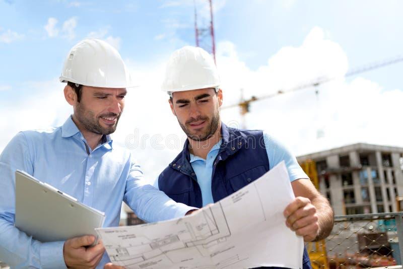 Ingenieur und Arbeitskraft, die Plan auf Baustelle überprüfen stockfotografie
