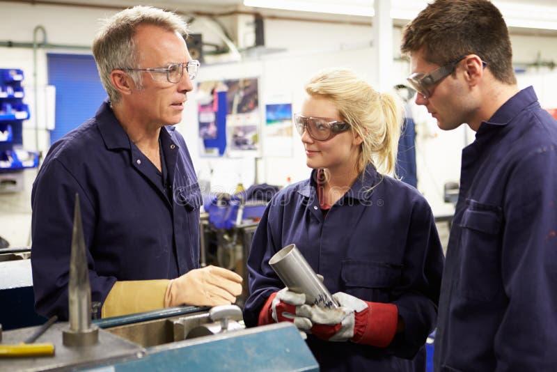 Ingenieur Working With Apprentices op Fabrieksvloer stock afbeelding