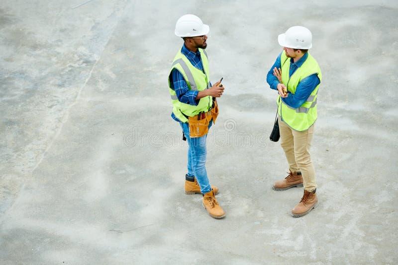 Ingenieure, die über Baustelle sprechen lizenzfreies stockbild