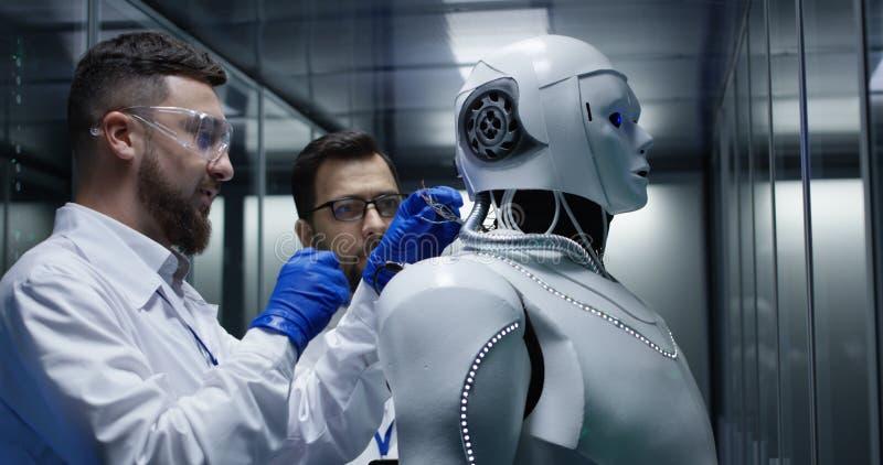 Ingenieure, die auf Roboterkontrollen prüfen stockfotografie