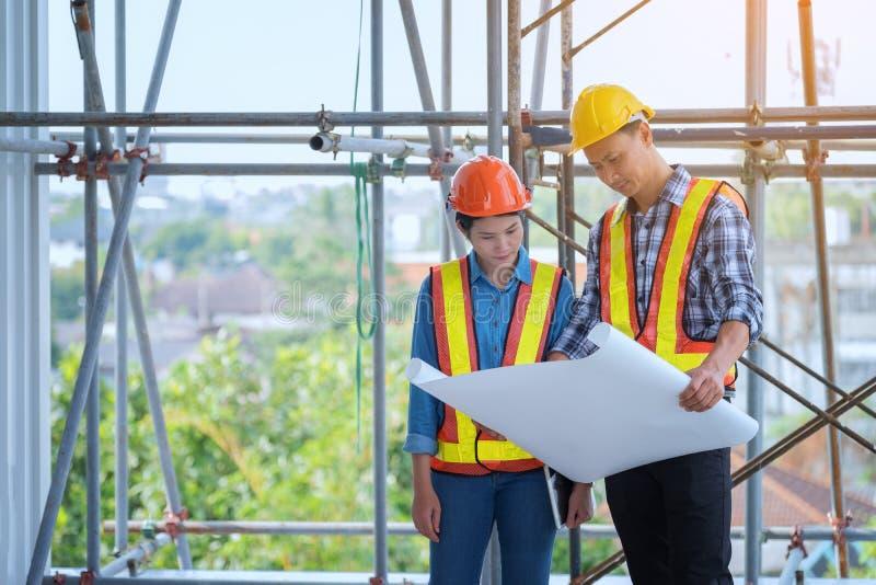 Ingenieure sind, schauend zu Hause treffend, bearbeitend und Plan herein lizenzfreie stockfotos