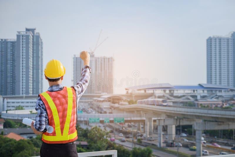 Ingenieure sind, schauend zu Hause treffend, bearbeitend und Plan herein stockbild