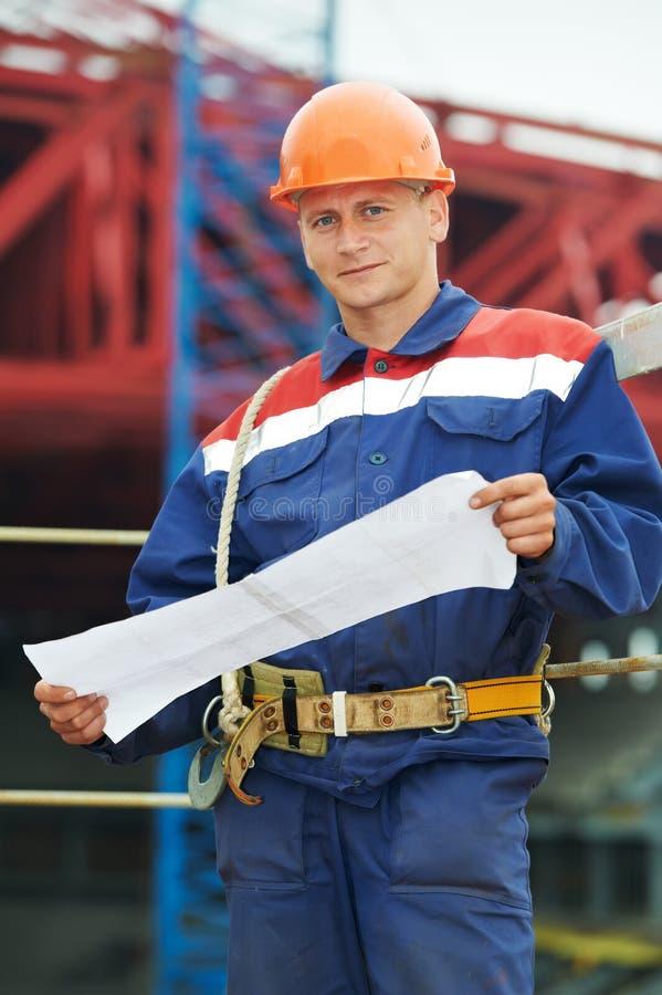 Ingenieurerbauer an der Baustelle mit Entwurf lizenzfreie stockfotografie