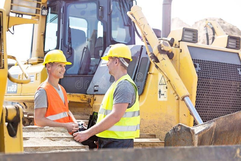Ingenieurs die bij bouwwerf bespreken stock afbeeldingen