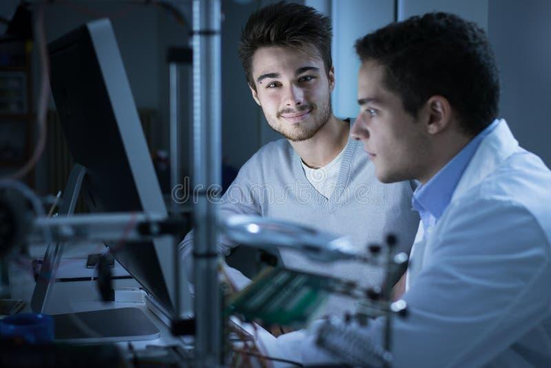 Ingenieurs die een computer met behulp van stock afbeeldingen