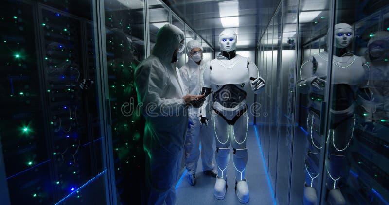 Ingenieurs die op robotcontroles testen binnen het laboratorium stock foto's