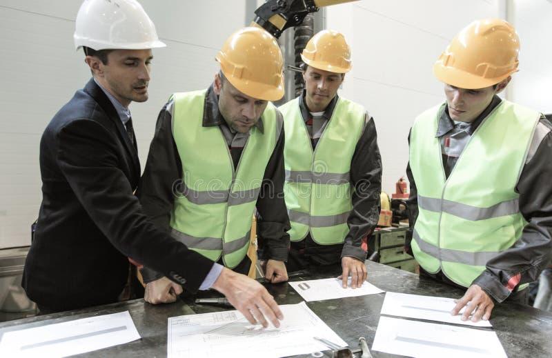 Ingenieursandworkers bespreken documenten stock afbeeldingen