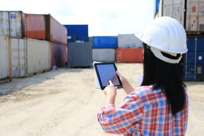 Ingenieurshand die digitale tablet met het lege scherm op voorcontainer en invoer-uitvoerachtergrond, Technologie en Zaken houdt royalty-vrije stock fotografie