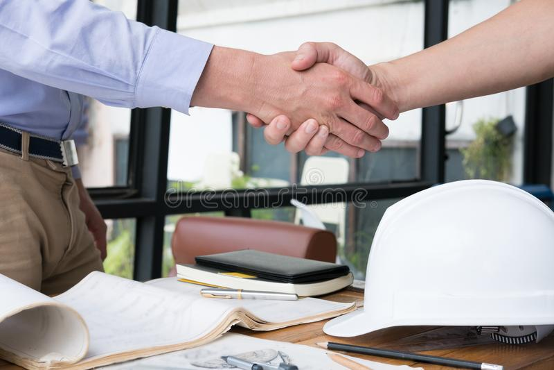 Ingenieurshandenschudden voor succesvolle overeenkomst in bouwplan A royalty-vrije stock fotografie