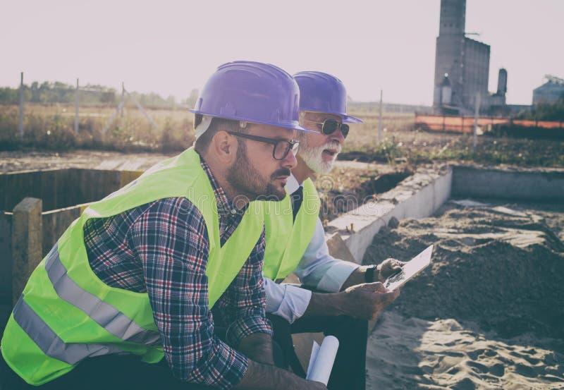 Ingenieurszitting bij bouwwerf en het denken stock fotografie