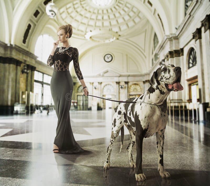 Ingenio que camina elegante de la señora joven el perro imágenes de archivo libres de regalías