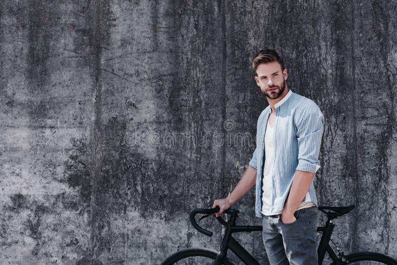 Ingenting jämför till det enkla nöjet av att rida en cykel Stilig brunhårig man med blåa ögon som står med a royaltyfria foton