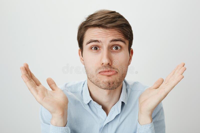 Ingenting kan göras Ståenden av den förvirrade attraktiva mogna mannen med borstet som rycker på axlarna och lyfter, gömma i hand arkivfoton