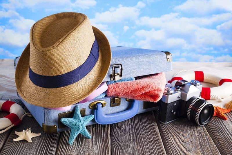 Ingepakte koffer voor de zomervakantie - hoed, handdoek, wipschakelaars en fotocamera op houten en strandachtergrond stock fotografie