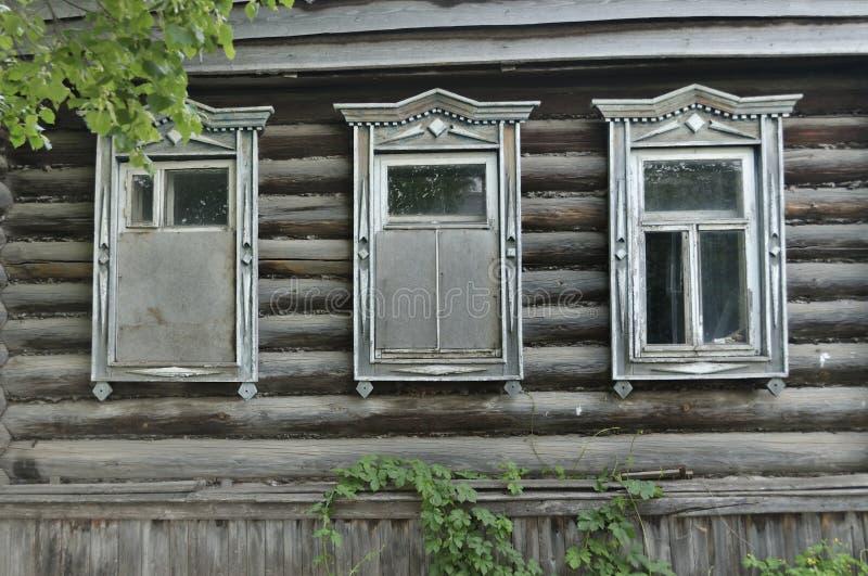 Ingescheept op vensters op de oude houten muur van het huis De gravure versiert het oude venster De muren van het huis van royalty-vrije stock foto's