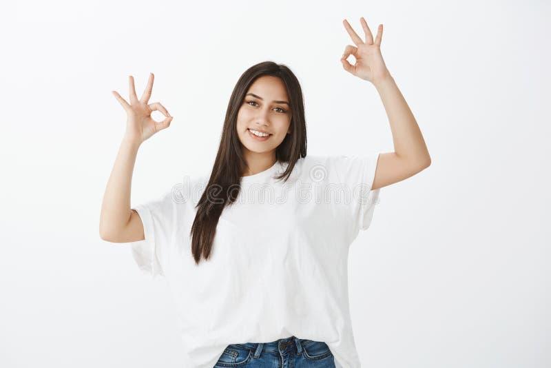 Inget bekymrat, allt ok Stående av realiteten som grinar den kvinnliga studenten i den vita t-skjortan som lyfter händer i ok ell arkivbilder